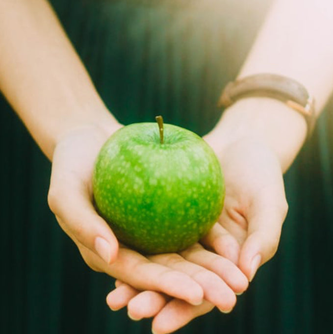 green apple in a girls hand