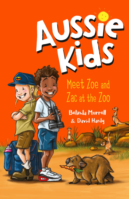 Image of Aussie Kids Meet Zoe and Zac illustrated front cover. Zoe and Zac are standing back to back near some hiking gear and a small wombat with a carrot in its mouth.