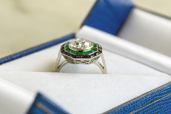 Octagonal shaped Platinum ring set with an old cut Diamond, surrounded by square cut Sapphires & Emeralds.