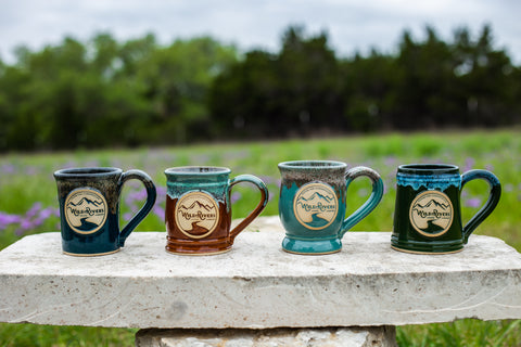4 different colored ceramic mugs displayed on a bench outdoors with a grassy background