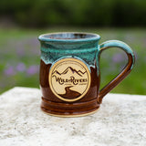 "Handmade, ceramic chestnut with green color 12 oz mug with Wild Rivers Logo and ""Coffee for Conservation"" on the center"