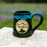 "Handmade, ceramic green with turquoise 12 oz mug with Wild Rivers Logo and ""Coffee for Conservation"" on the center"