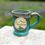 "Handmade, ceramic teal with rust color 12 oz mug with Wild Rivers Logo and ""Coffee for Conservation"" on the center"