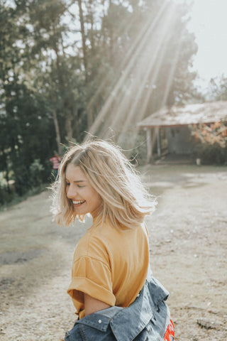 a smiling woman standing outside wearing a t-shirt with sun rays beaming onto her head