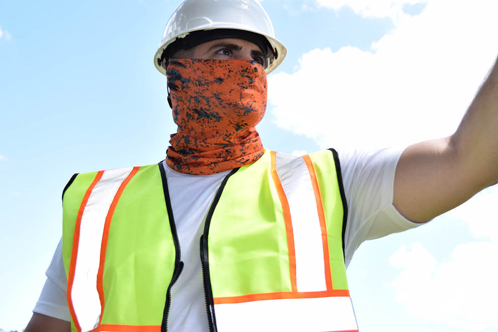 a man in an Oblast face guard in a hard hat and reflective vest against a blue sky. OBlast is a bright orange Face Guard with black and grey specks dotted on it.