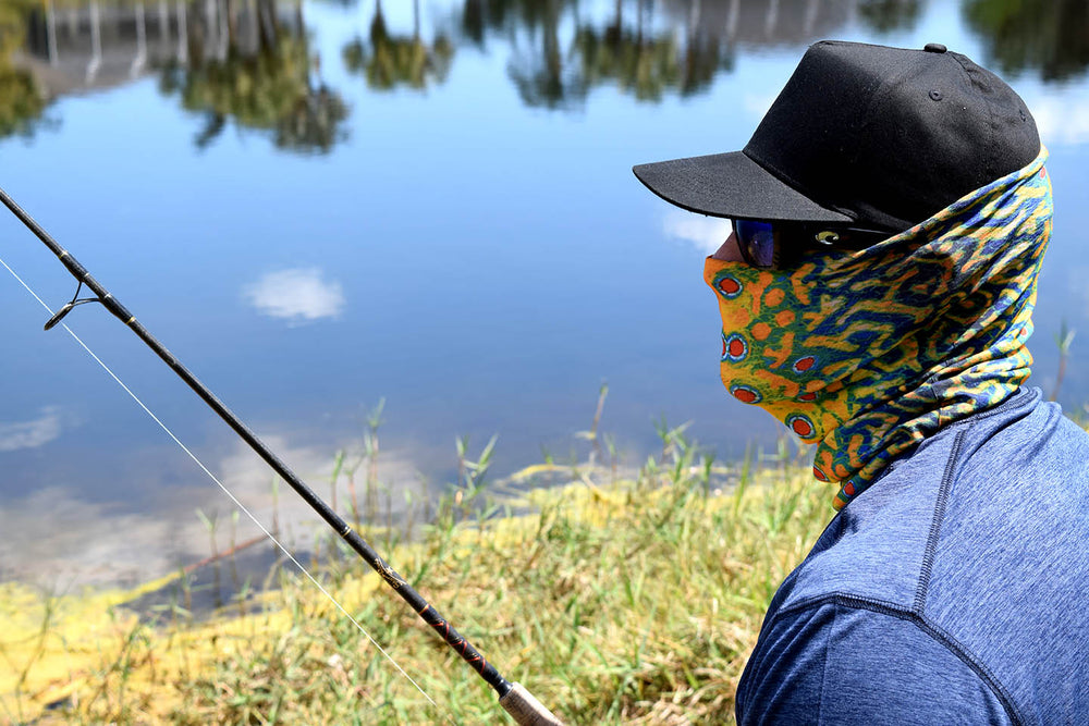A man fishing with a Firefly Face Guard on. Firefly is a multi colored style with green, blue, yellow and red like a pattern on a fish.