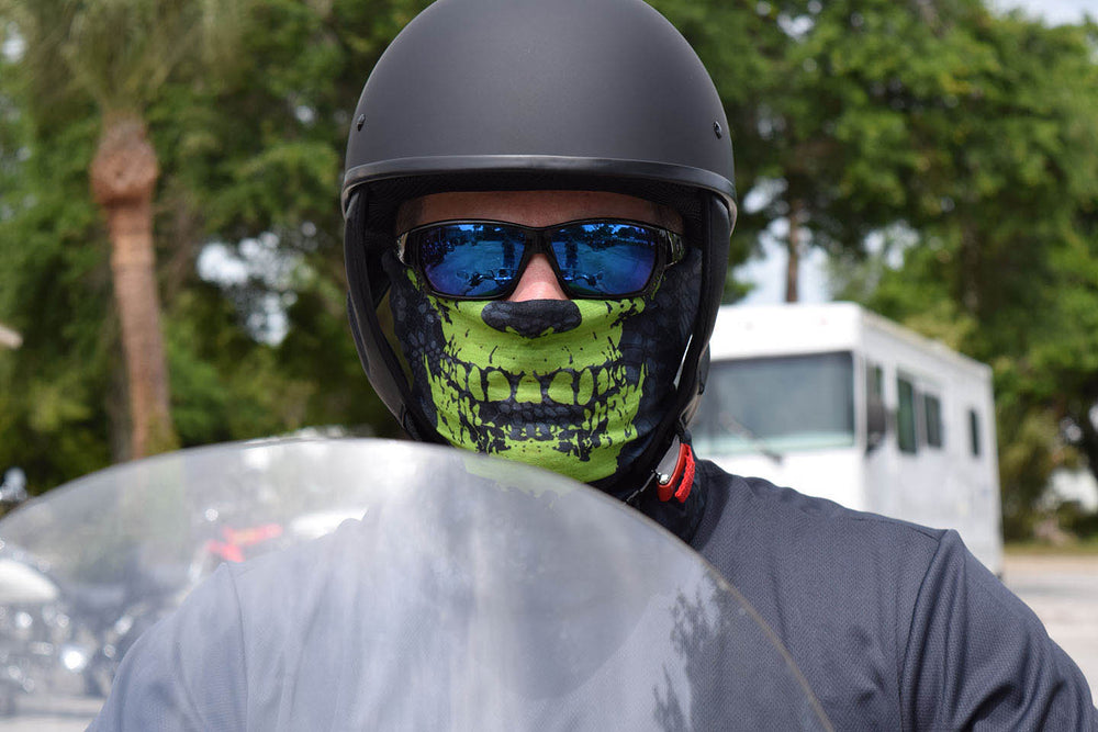 A man on a motorcycle with a helmet on wearing the Toxic Face Guard. The Toxic Face Guard features a lime green skull on a grey textured background. When worn it looks like your nose and mouth are a skull.