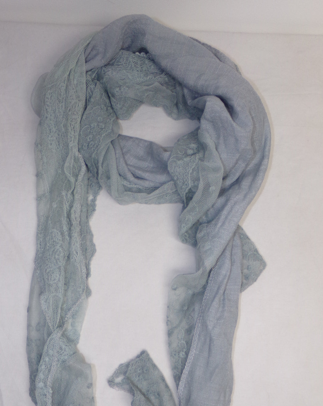 A  scarf with a teal colour finish. A plain and lace effect pattern provide a delicate and feminine finish.  A lightweight versatile accessory to the wardrobe that would compliment a top, dress, coat or jacket.