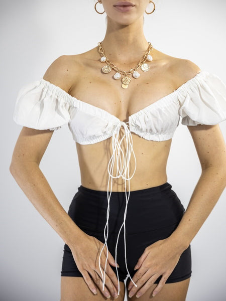 Image displays that the puff sleeves can be worn off shoulders.Floating On a Dream Bralette Top in White. Featuring puff shoulder sleeves and front bow lace up design.