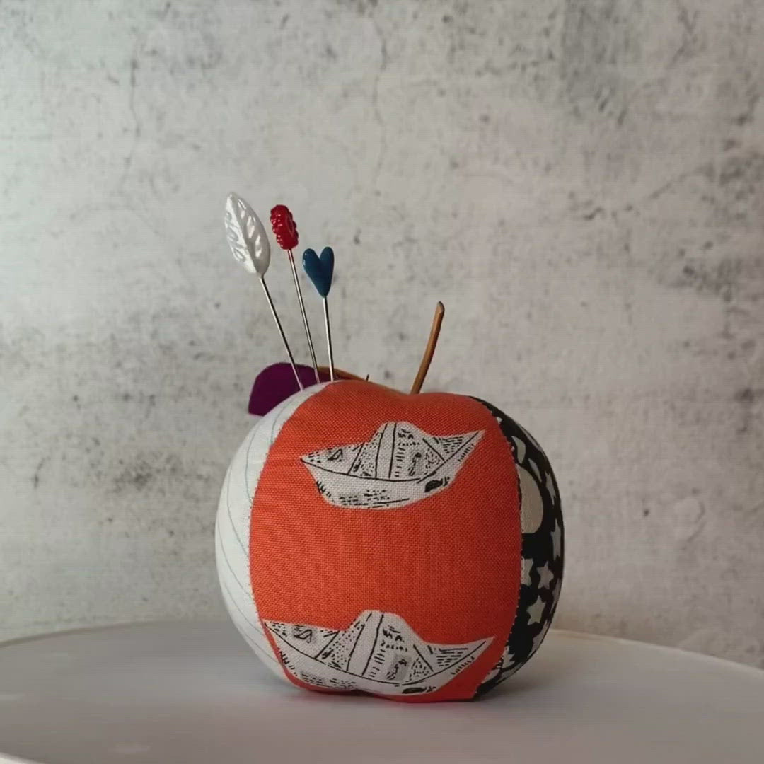 Apple pincushion video - orange fabric with paper hats and black and white prints
