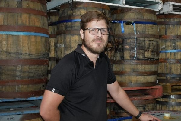 Max Casey with barrels in the background