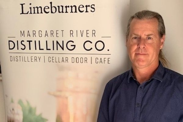Paul Burke next to the Limeburners and Margaret River Distilling Co logo