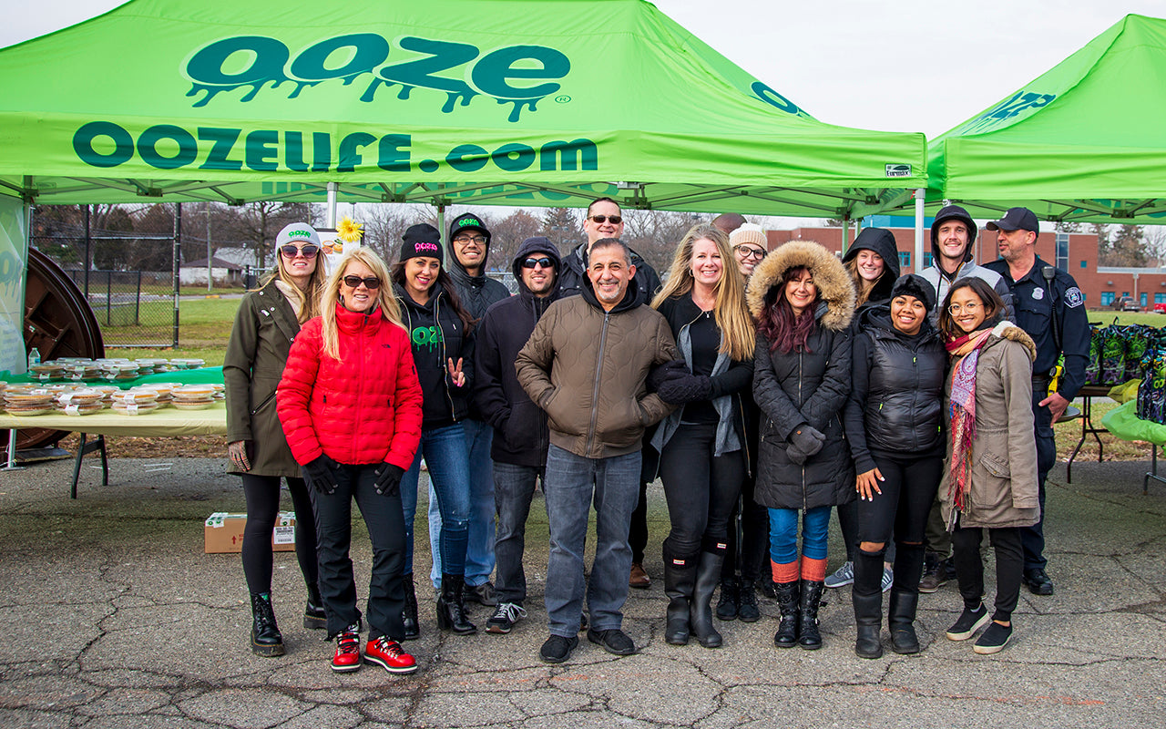 The Ooze Wholesale team is standing in front of their tents at the Oozegiving event. 200 turkeys, pies and side dishes were distributed as a Thanksgiving feast for 200 Detroit families in need.