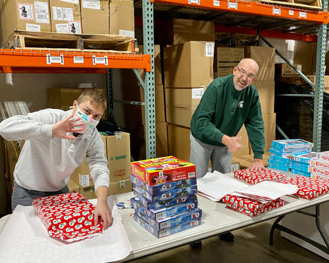 A younger guy and older bald man are standing at a folding table in the Ooze Wholesale warehouse wrapping gifts. They have a pile of games on the table and rolls of wrapping paper, they are actively wrapping the gifts.