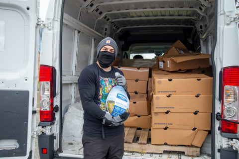 An Ooze Foundation team member wearing black clothes and a black face mask holds up a turkey in front of the trunk of a white van filled with boxes of turkeys.