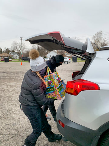 Ooze Foundation team members load a Thanksgiving dinner into a car trunk. They are wearing winter clothes and masks, and have a turkey and bag of side dishes in hand.