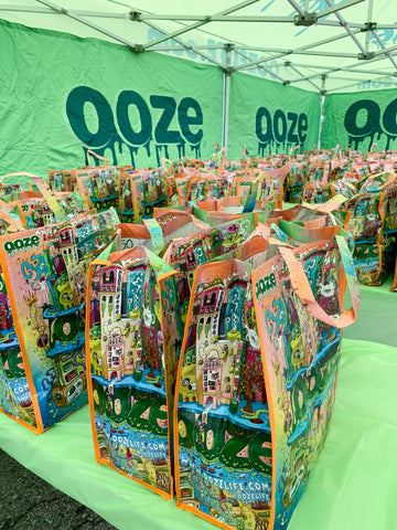 Tables in the green Ooze tent are full of Ooze bags that are filled with Thanksgiving side dishes to be donated for Oozegiving.