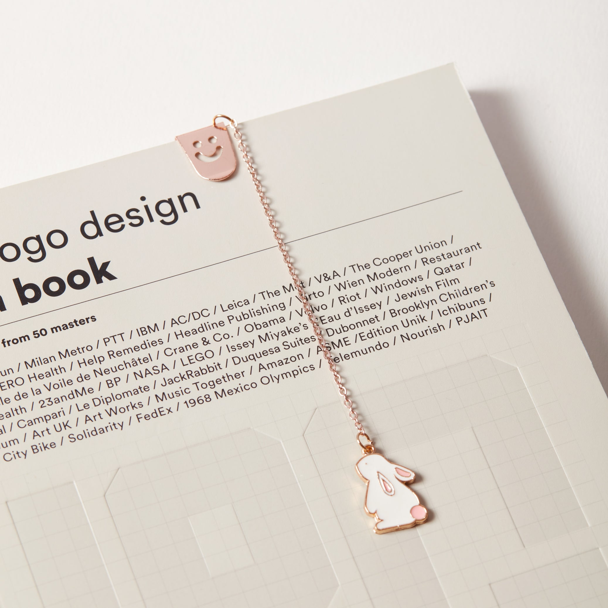 Enamel metal bunny charm bookmark clipped onto a book cover.