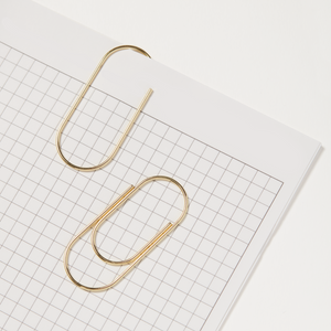Large Gold Metal Paper Clips On Paper