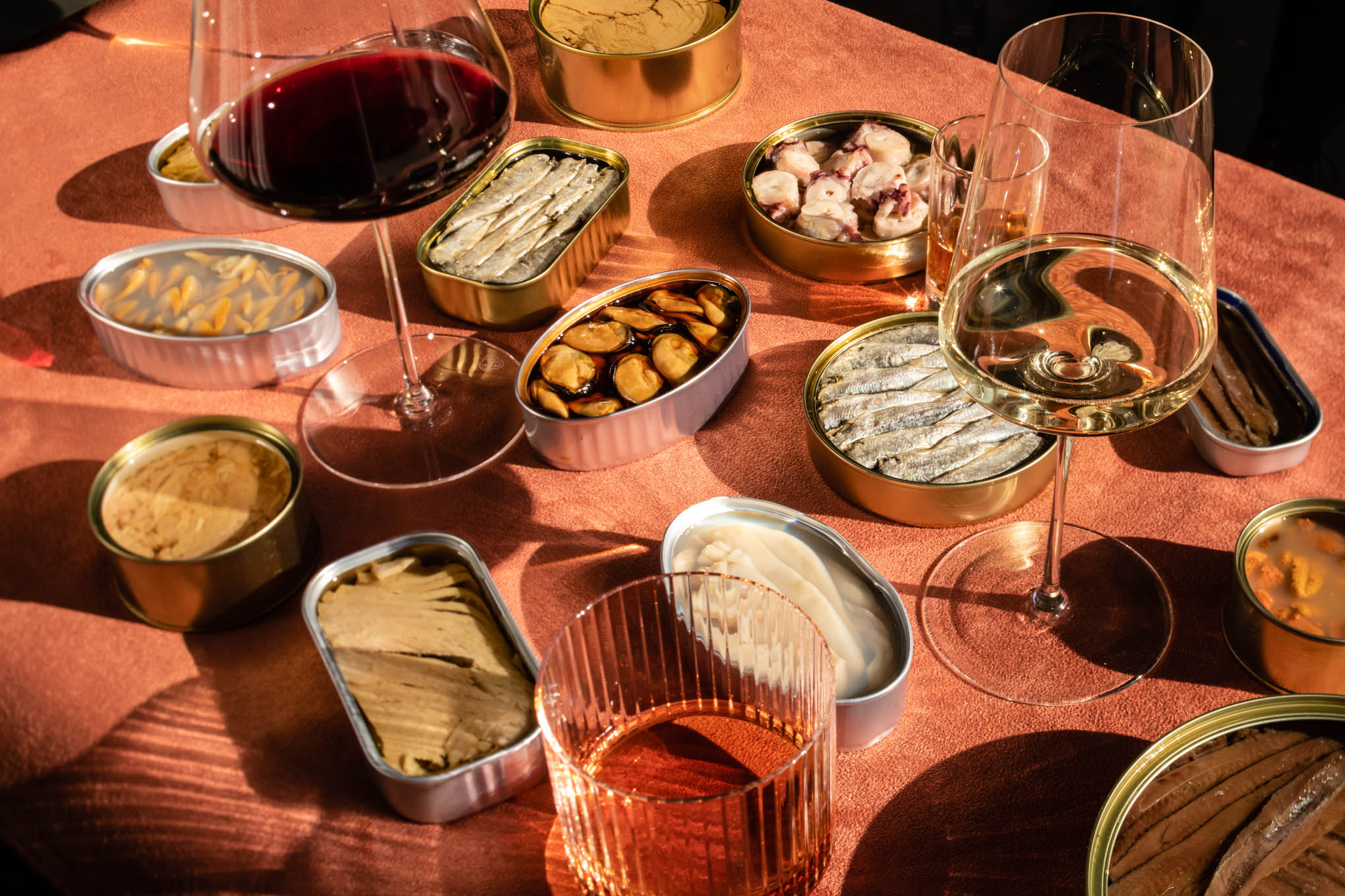 A large variety of seafood conserva cans opened amongst wine glasses on a pink surface