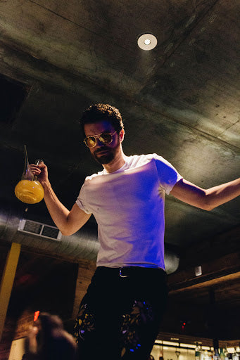 Drew McConnell standing on a bar and holding a porron in his hand