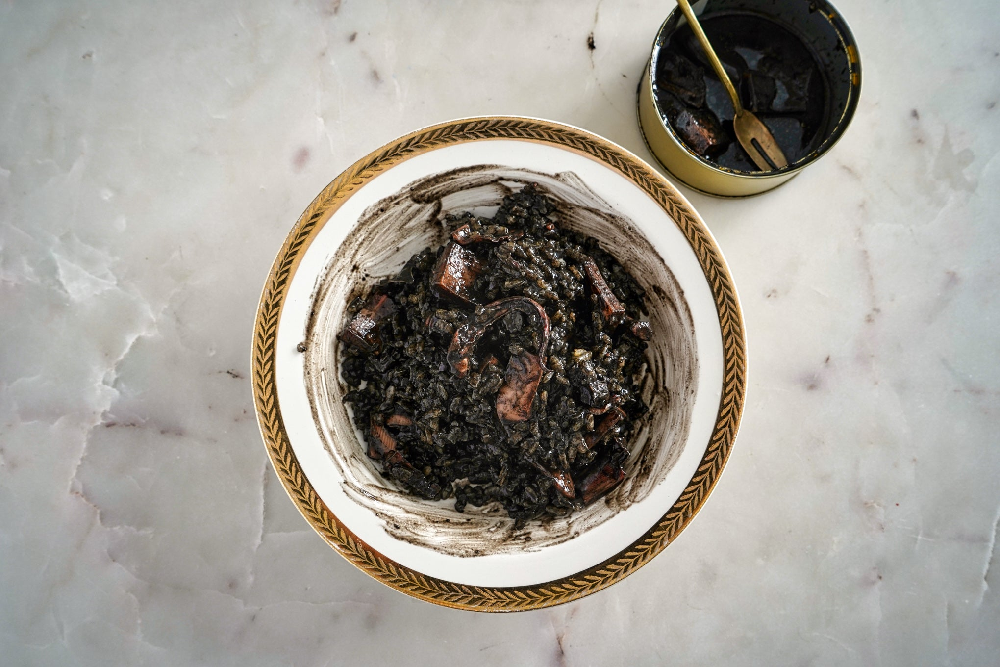 open can of calamar and completed recipe of arroz negra