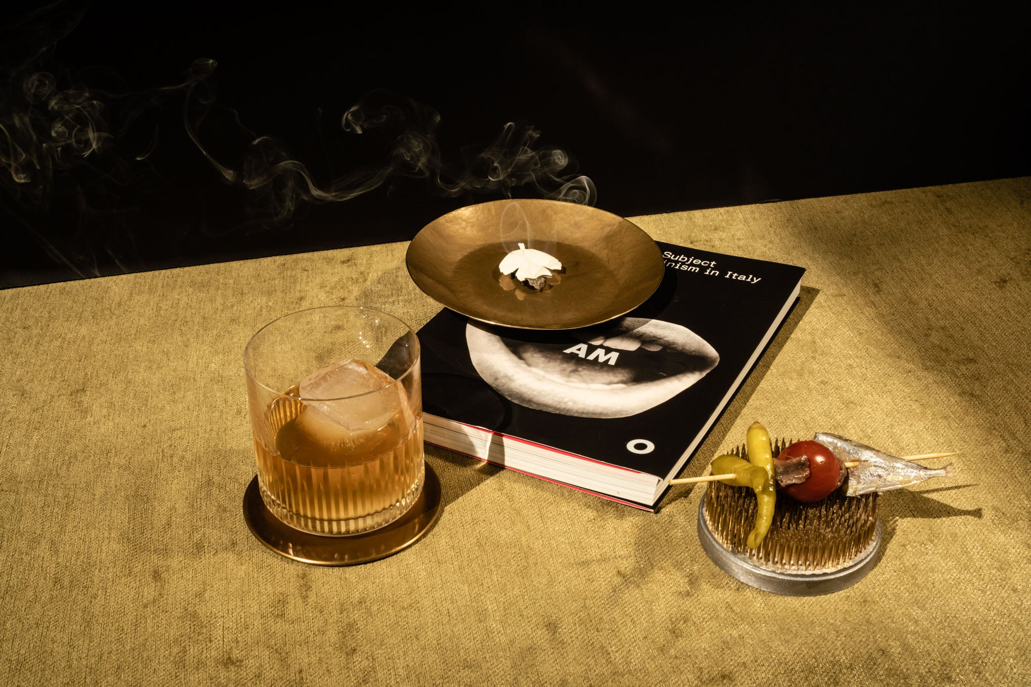Glass of liquor, burning white leaf, book, and peppers on a table