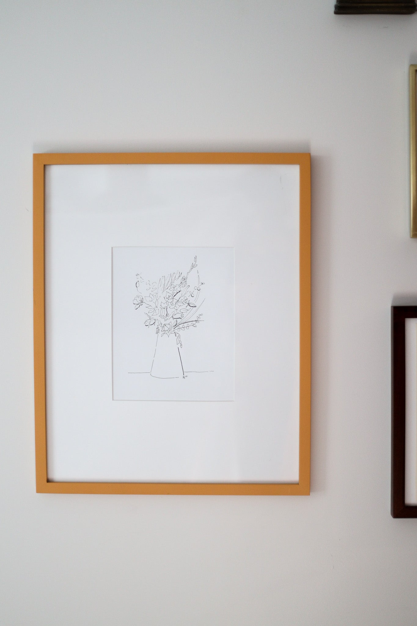 Orange framed floral sketch hanging on the wall