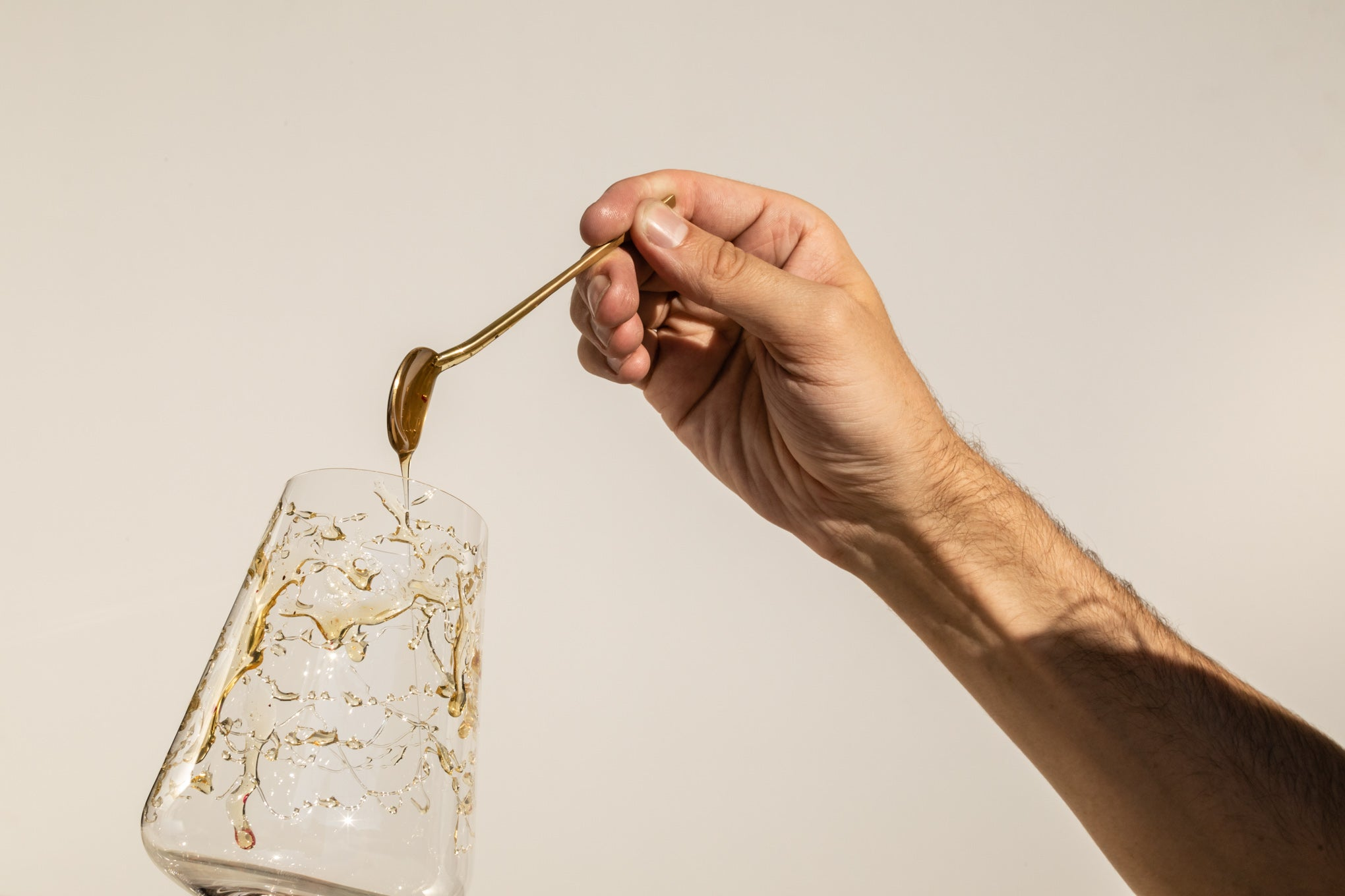 Pouring Rose Gold Wildflower Honey onto wine glass