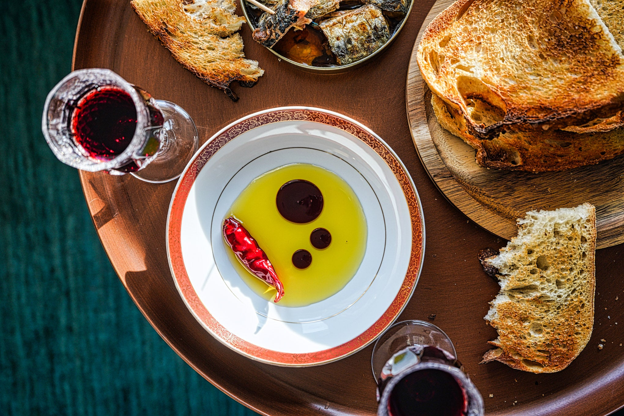 olive oil and vinegar in dish with chili pepper, on brass table with toasted bread and red wine