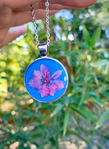 Blue round pendant with pink pressed flower