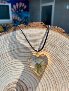 Gold heart shaped pendant with pressed flower
