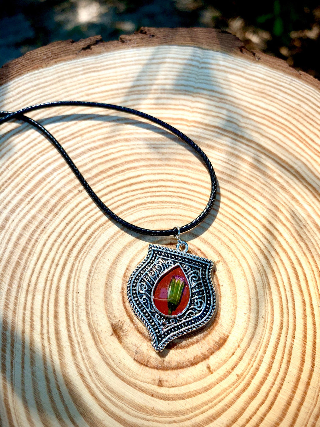 Silver and red pendant with pressed flower