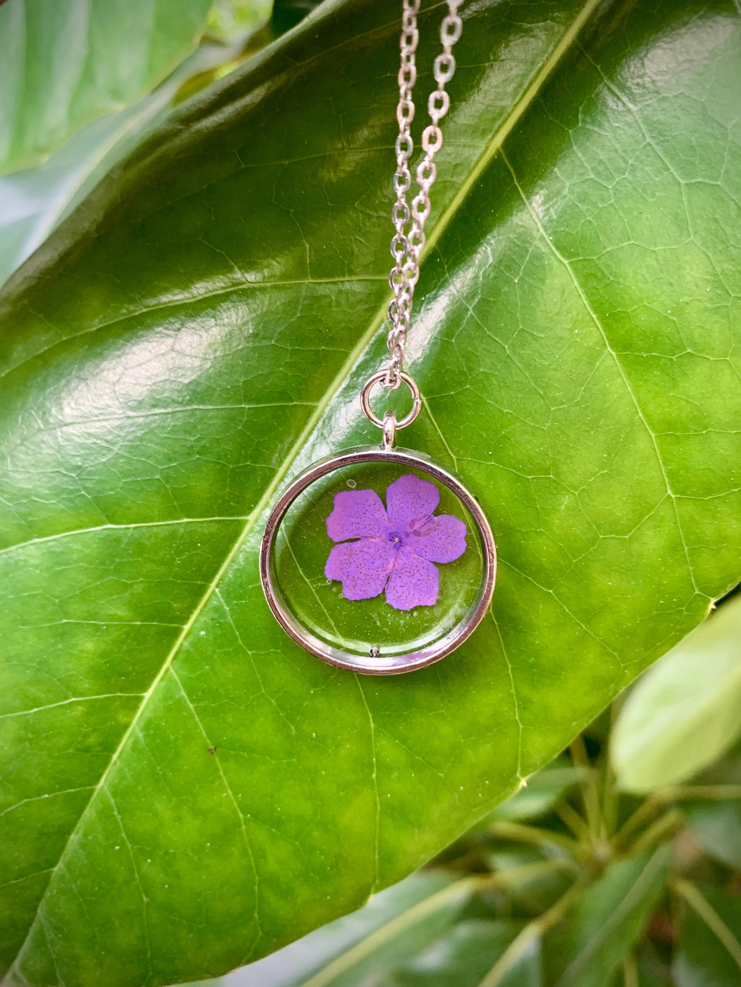 Circular silver pendant with purple pressed flower
