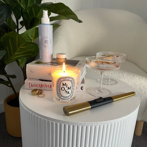 Saint Jack Makeup Cleaning Mist, Diptyque Mimosa Candle, Flint Rechargeable Lighter and Decorative items sit on DIY ottoman