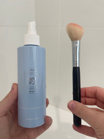 Saint Jack Makeup Cleaning Mist and woman's hand holding a dirty blush brush