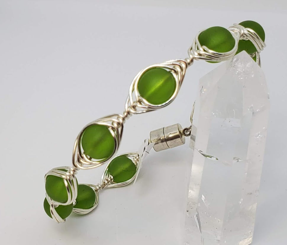 Green Sea Glass with herringbone wrapped wire. 20 gauge artistic wire in silver with magnetic clasp. Very attractive Bangle style