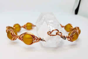 Amber colored Sea Glass wrapped in a herringbone copper wire with handmade hook clasp.