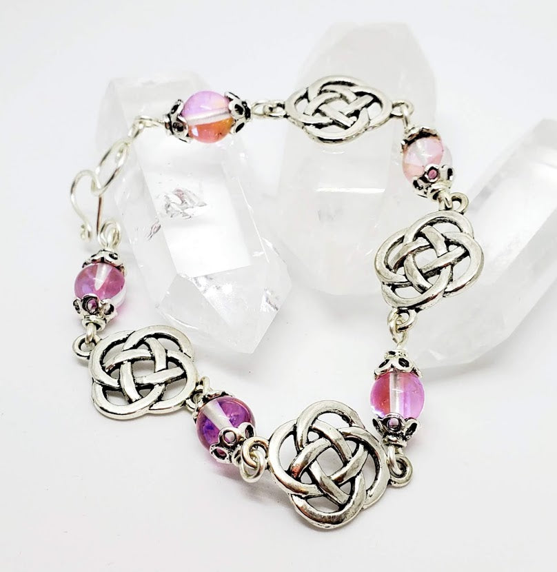 "8 "" Celtic Themed Bracelet with handmade hook/eye clasp. The Pink illuminate bead flickers in the light. Made with nickel free silver tone metal."