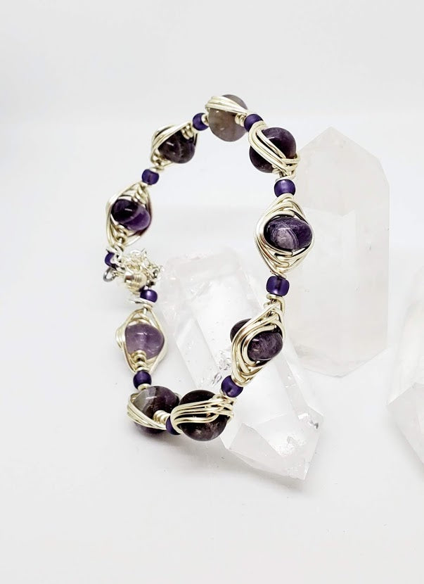 10mm rondell Amethyst Gemstone wrapped in 18 gauge artistic wire. Magnetic clasp with safety chain. Fits average wrist of 7 inches This bracelet has a bold look with the 18 g wire.