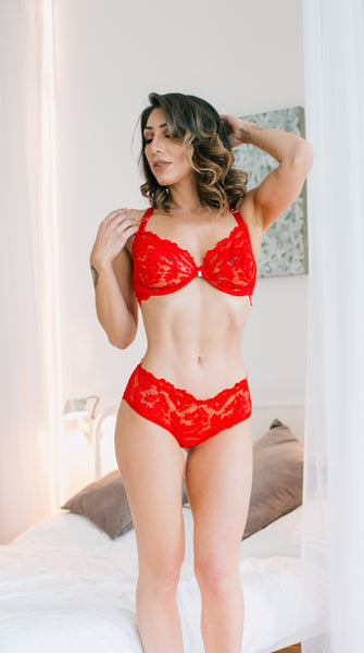 Red stunning plunge front fastening soft cup bra with centre diamante detail. This unusual halter neck design features an adjustable neck strap. The back has a lace under band which has a 3-strap detail across the back fastening to a stunning piece of matching lace at the neck.