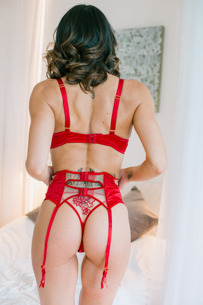 Red suspender belt is decorated with many panels with a range of delicate intricate mesh and soft to touch satin-like material. A lovely crinkled effect has been created by the stitching on edge of the front nude mesh panel. The suspender belt has adjustable straps. Also available in black