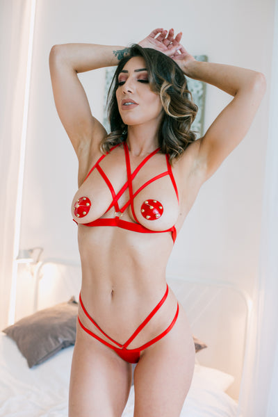 Red risque bra and thong set. Features an open cup chest with an involved pattern of elasticated straps as pictured. At the back of the neck is a fastening feature and an adjustable slider to adjust where appropriate. A matching thong is also included which has satin material.