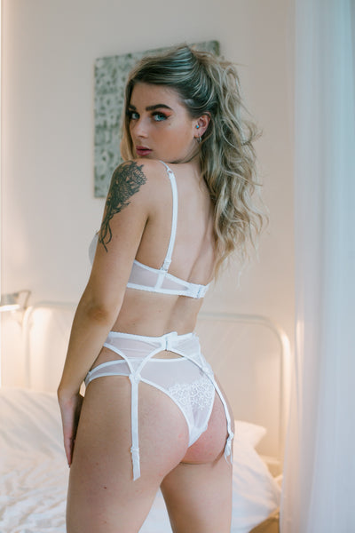 A very delicate white thong, the front is ornamented with foliage embroidery. Jonquil matching bra and suspender belt sold separately .