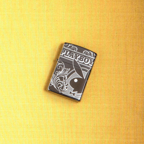 Lifestyle image of Playboy 360° Design Windproof Lighter laying on a yellow background