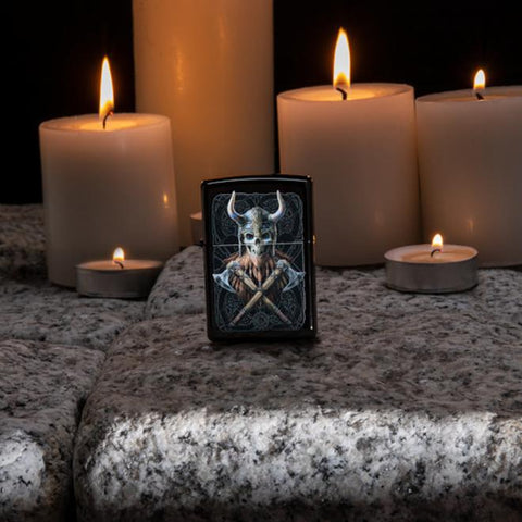 Lifestyle image of Anne Stokes Viking Skull Lighter standing on cobblestone with lit candles in the background