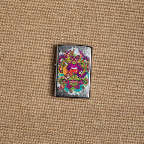 Lifestyle image of Psychedelic Lip Design Street Chrome Lighter laying on hemp fabric