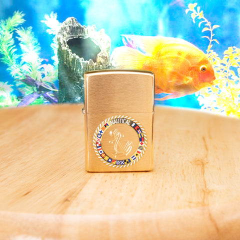 Lifestyle image of Nautical Flags Design Brushed Brass Windproof Lighter with oceanic scene in the background