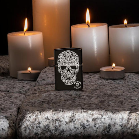 Lifestyle image of Anne Stokes Fancy Skull Lighter standing on cobblestone with lit candles in the background