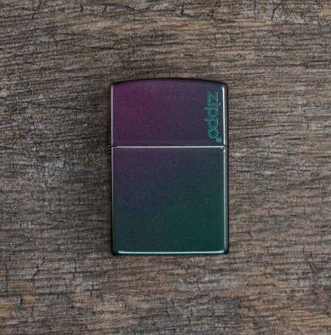 Lifestyle image of Iridescent Zippo Logo Windproof Lighter laying flat on a wooden surface